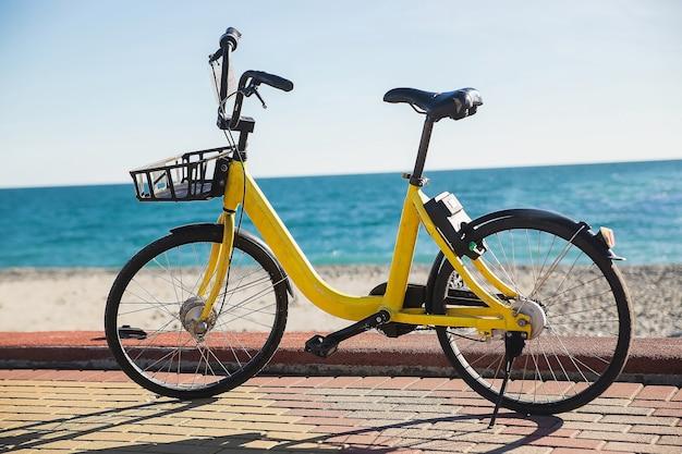 Bici gialla che si appoggia accanto al palo di cemento sul mare blu della spiaggia Foto Premium