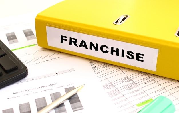 Una cartella gialla con i documenti etichettati franchise si trova sulla scrivania dell'ufficio con i grafici finanziari Foto Premium