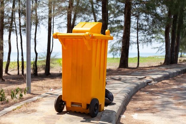 Bidoni della spazzatura gialli nel parco vicino al mare. Foto Premium