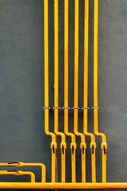Il tubo del gas giallo con una gru percorre la facciata di un nuovo edificio a più piani. Foto Premium