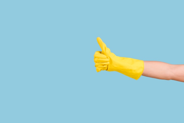 Mano gialla dei guanti che mostra pollice sul gesto contro il fondo blu Foto Premium