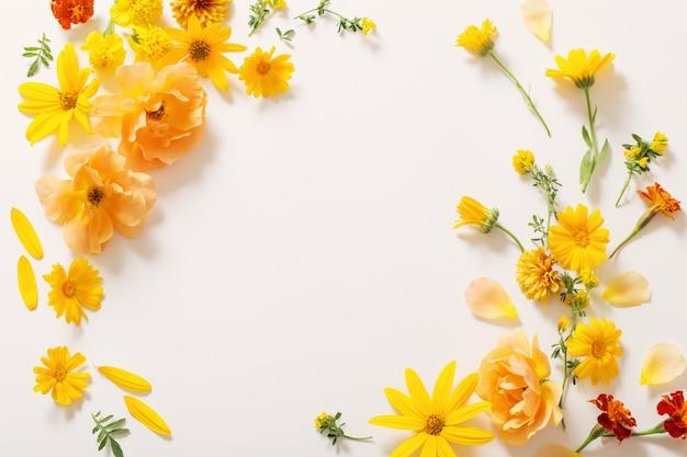 Fiori gialli ed arancioni sulla parete bianca Foto Premium