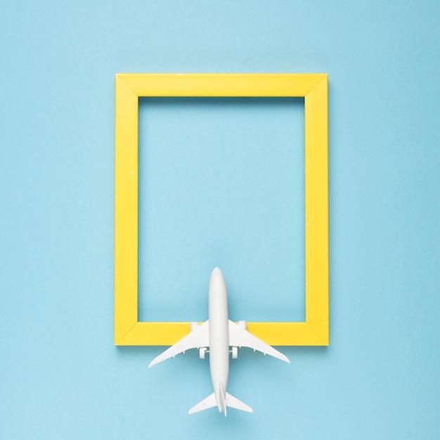 Cornice rettangolare gialla vuota e aereo Foto Premium