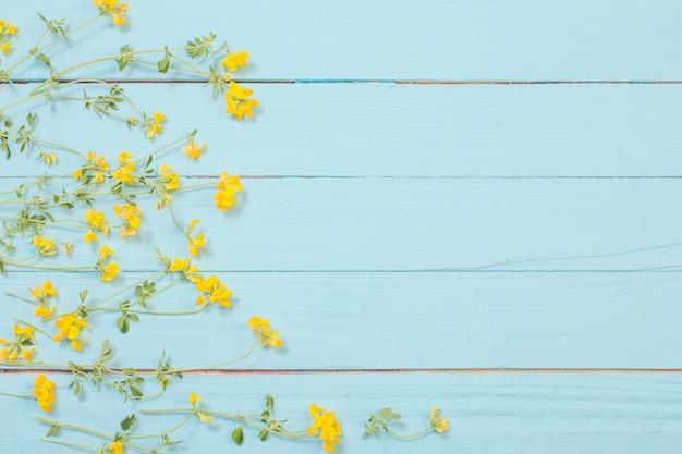 Fiori selvatici gialli su fondo di legno blu Foto Premium