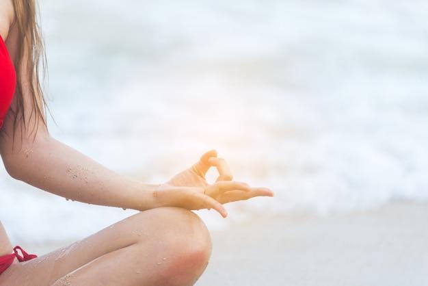 Yoga stile di vita fitness sulla spiaggia donna sana relax facendo meditazione. yoga meditando all'aperto con zen in posizione seduta. illuminismo fitness giovane felicità concentrare il concetto di esercizio Foto Premium