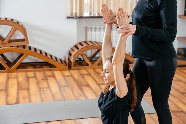 L'insegnante di yoga sta aiutando la giovane donna a fare pose in palestra Foto Premium