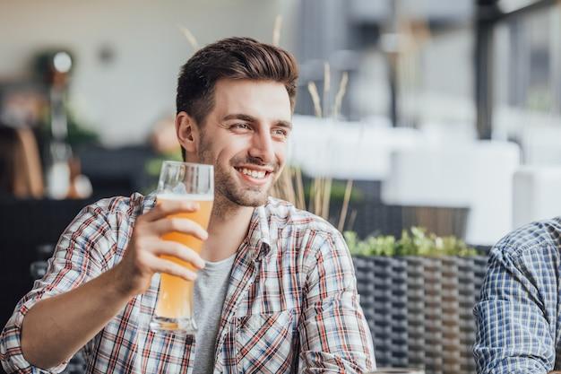 Yong bellissimo uomo che beve birra dopo un duro lavoro Foto Premium