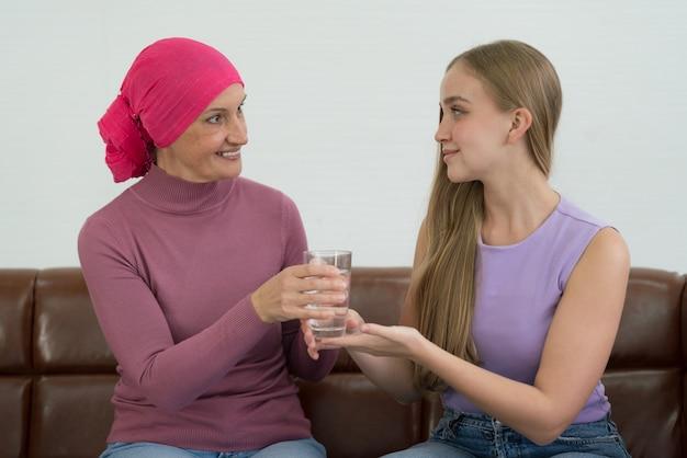 Paziente di cancro della giovane femmina adulta che trascorre del tempo con sua figlia a casa. Foto Premium