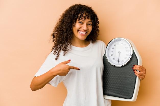 Giovane donna afroamericana afro che tiene una persona di scala che indica a mano uno spazio della copia della camicia, orgoglioso e fiducioso Foto Premium