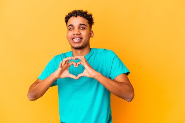 Giovane uomo afroamericano riccio isolato su viola sorridente e mostrando una forma di cuore con le mani. Foto Premium