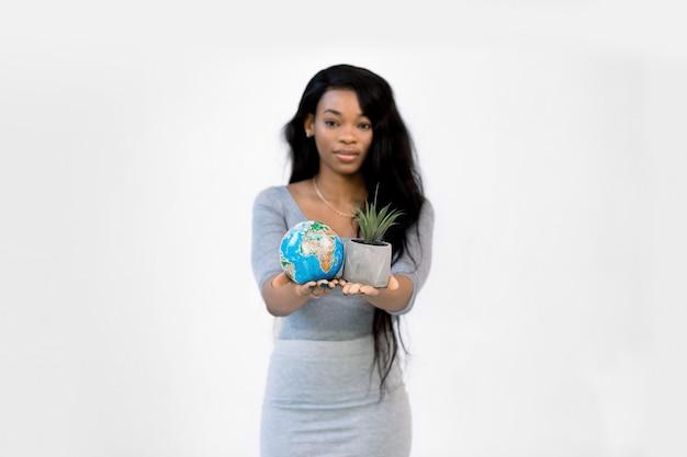 Giovane donna afroamericana che mostra poco globo terrestre in una mano e piccolo vaso grigio con pianta in un altro Foto Premium