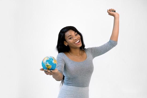 Giovane condizione africana della donna isolata sul globo bianco della terra del litlle della tenuta della parete Foto Premium
