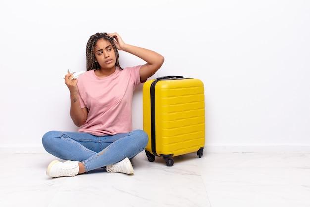 Giovane donna afro che si sente perplessa e confusa, grattandosi la testa e guardando di lato. concetto di vacanze Foto Premium