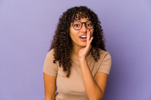 La giovane donna afro isolata sta dicendo una notizia segreta di frenata calda e sta guardando da parte Foto Premium