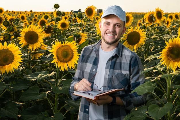 Giovane agronomo ispezionando i girasoli in campo Foto Premium
