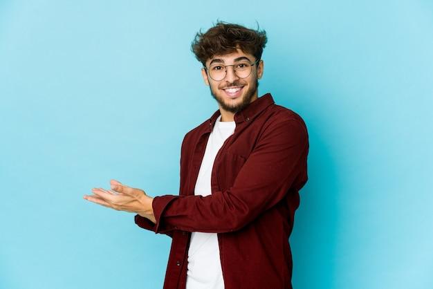 Giovane uomo arabo sull'azzurro che tiene uno spazio della copia su una palma. Foto Premium