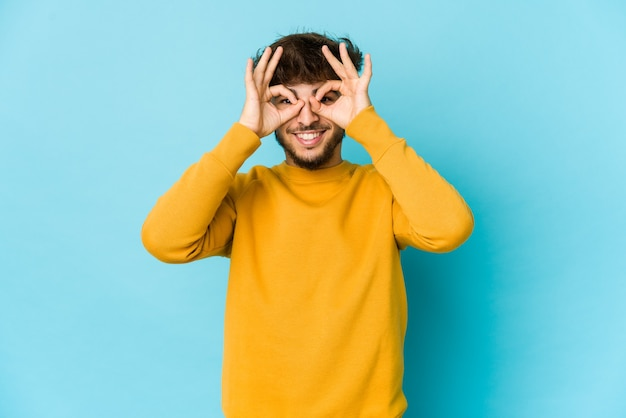 Giovane uomo arabo sull'azzurro che mostra segno giusto sopra gli occhi Foto Premium
