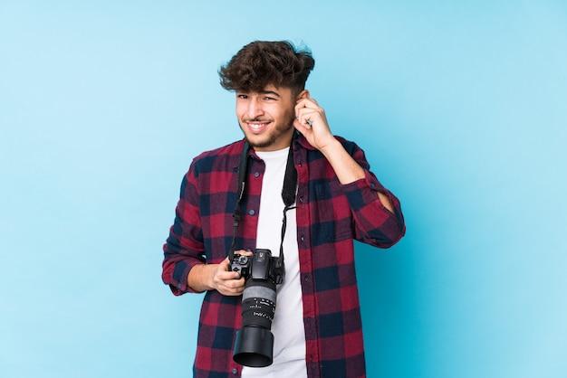 Giovane fotografo arabo uomo isolato che copre le orecchie con le mani. Foto Premium