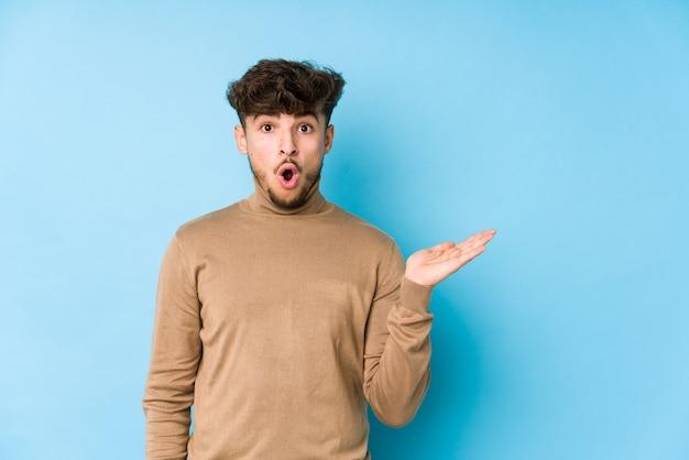 Il giovane arabo ha isolato lo spazio della copia della tenuta impressionato sul palmo. Foto Premium
