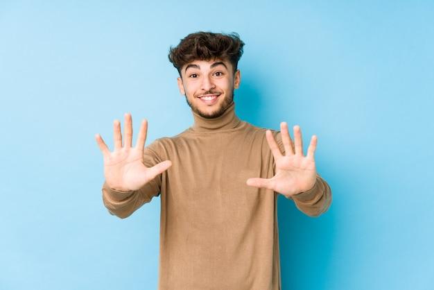 Giovane uomo arabo isolato che mostra il numero dieci con le mani. Foto Premium