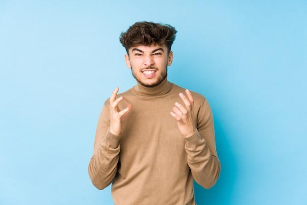 Giovane uomo arabo isolato sconvolto urlando con le mani tese. Foto Premium