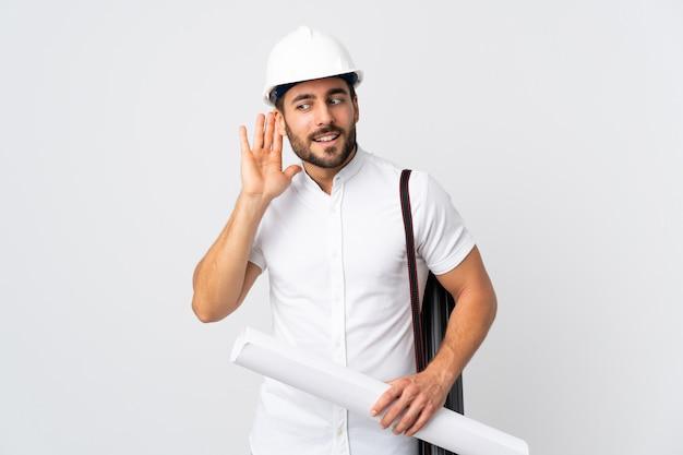 Giovane uomo dell'architetto con il casco e giudicare i modelli isolati sulla parete bianca che ascolta qualcosa mettendo la mano sull'orecchio Foto Premium