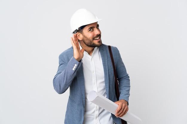Uomo del giovane architetto con il casco e che tiene le cianografie isolate sulla parete bianca che ascolta qualcosa mettendo la mano sull'orecchio Foto Premium