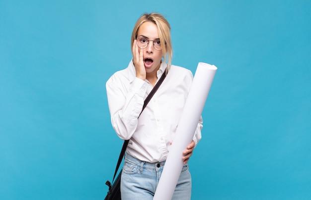 Giovane donna architetto che si sente scioccata e spaventata, sembra terrorizzata con la bocca aperta e le mani sulle guance Foto Premium