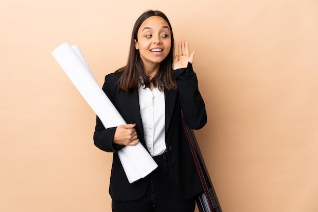 La giovane donna dell'architetto tiene i modelli sopra la parete isolata che ascolta qualcosa mettendo la mano sull'orecchio Foto Premium