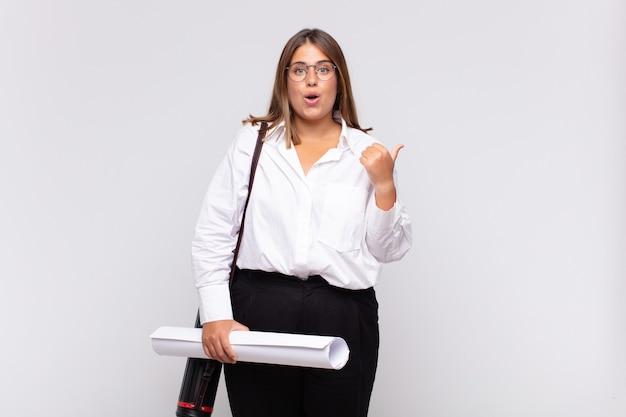 Giovane donna architetto che guarda stupita incredula, indicando un oggetto sul lato e dicendo wow Foto Premium