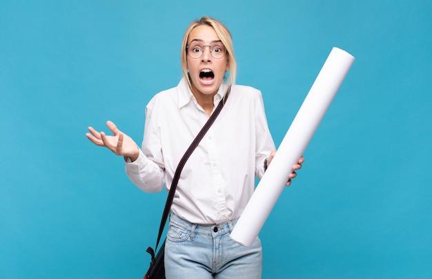 Giovane donna architetto a bocca aperta e stupita, scioccata e sbalordita da un'incredibile sorpresa Foto Premium