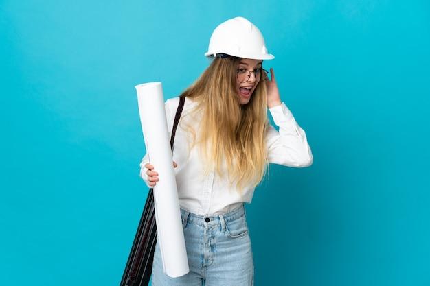 Giovane donna dell'architetto con il casco e che tiene le cianografie sull'azzurro che ascolta qualcosa mettendo la mano sull'orecchio Foto Premium