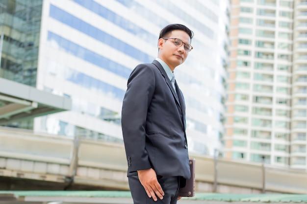Giovane uomo d'affari dell'asia in vestito con il suo computer portatile all'aperto Foto Premium