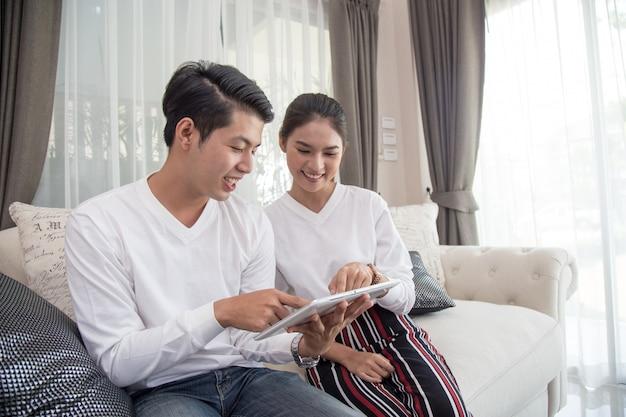 Giovani coppie asiatiche che utilizzano compressa digitale sul sofà a casa. Foto Premium