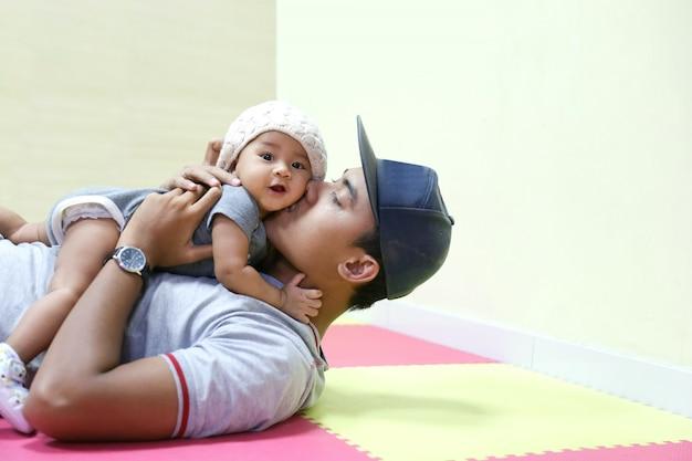 Giovane padre asiatico che tiene e che bacia bambino adorabile Foto Premium