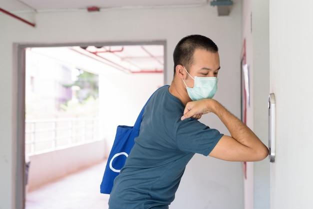 Giovane uomo asiatico con maschera premendo il pulsante dell'ascensore con il gomito per prevenire la diffusione del coronavirus Foto Premium