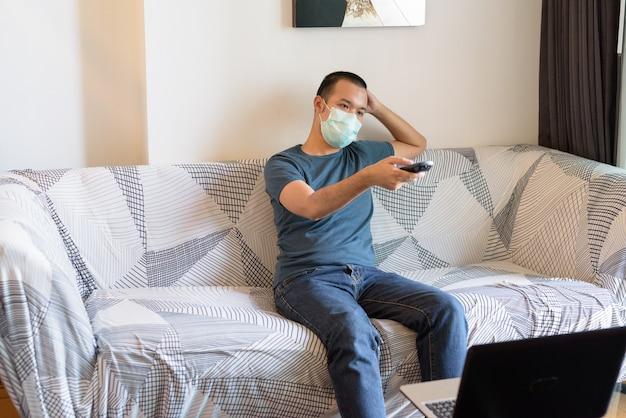 Giovane uomo asiatico con maschera guardando la tv a casa in quarantena Foto Premium