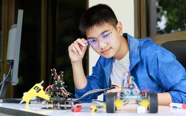 Il giovane adolescente asiatico gode con l'officina dell'automobile del giocattolo. Foto Premium