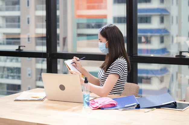 Giovane donna asiatica in casual con maschera facciale e nota di pianificazione sul calendario presso il nuovo ufficio normale Foto Premium