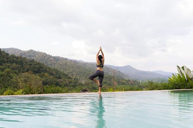 Giovane donna asiatica che fa esercizio di yoga all'aperto vicino alla piscina Foto Premium