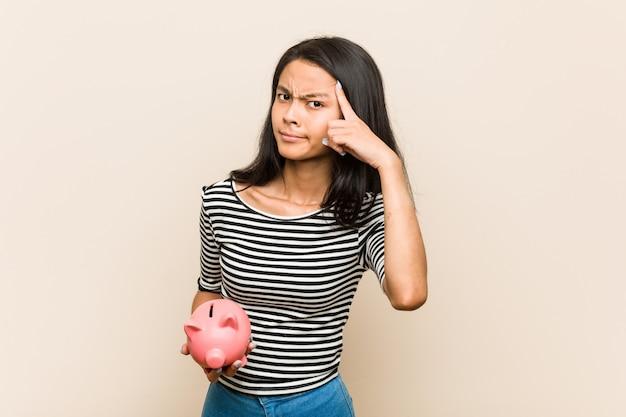 Giovane donna asiatica che tiene un porcellino salvadanaio che mostra un gesto di delusione con l'indice. Foto Premium