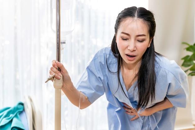 Dolore di camminata e periodo paziente della giovane donna asiatica nella stanza di ospedale. Foto Premium