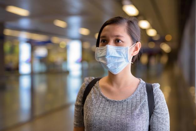 Giovane donna asiatica con maschera in piedi dalla luce presso la stazione della metropolitana Foto Premium