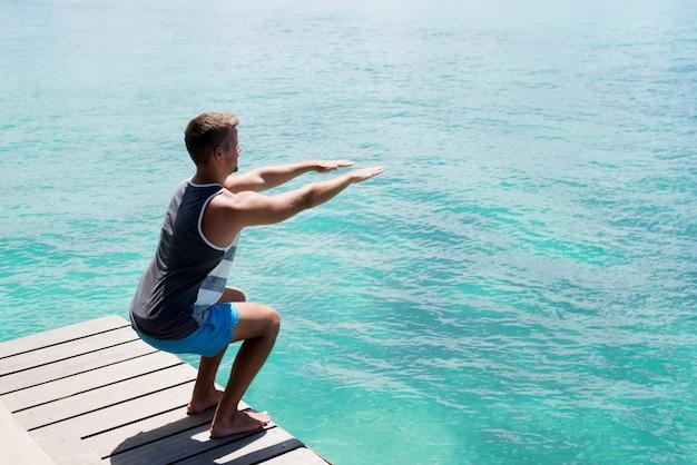 Giovane atleta che fa squat sul bacino del mare. sano stile di vita estivo. Foto Premium