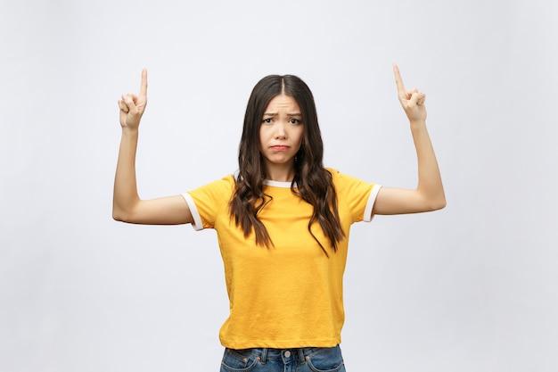 Giovane donna asiatica attraente che indica il dito con emozione infelice Foto Premium
