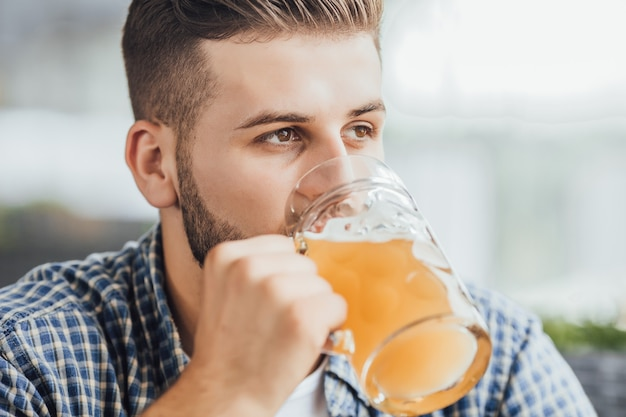 Giovane ragazzo attraente che beve birra al caffè dopo il lavoro Foto Premium
