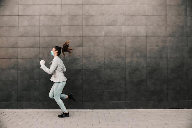 Giovane brunetta attraente vestita casual elegante con maschera facciale sul correre sul lavoro durante l'epidemia di virus corona. Foto Premium