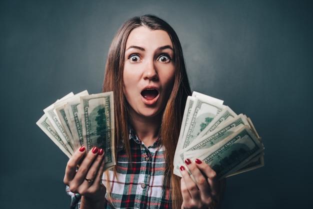Giovane donna attraente con indifferenza vestita che sembra scioccata tenendo le banconote in dollari nelle mani Foto Premium