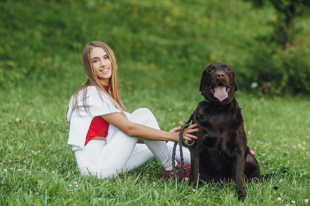Giovane ragazza attraente che si siede sull'erba con la sua migliore amica Foto Premium