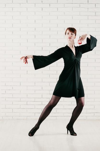 Giovane donna attraente in abito nero, ballando con nacchere rosse Foto Premium